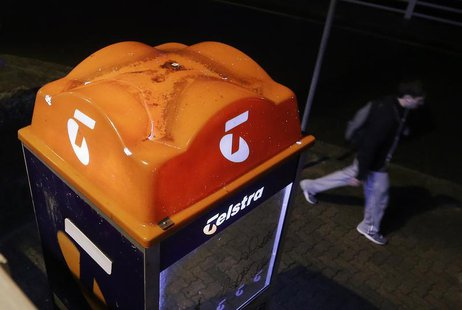 A man walks past a Telstra public phone in Sydney August 8, 2013. REUTERS/Daniel Munoz