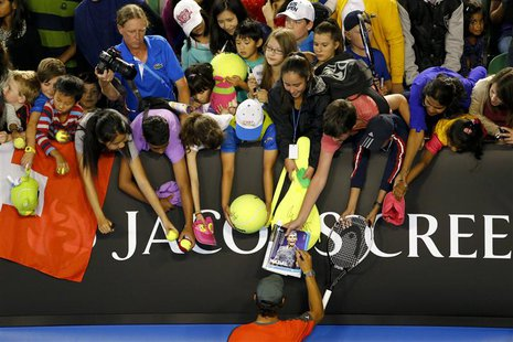 Rafael Nadal of Spain signs autographs for fans during the Kids Tennis Day before the Australian Open 2014 tennis tournament in Melbourne, J