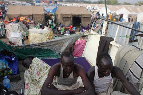 Displaced men rest in an improvised shelter at Tomping camp, where some 17,000 displaced people who fled their homes are being sheltered by