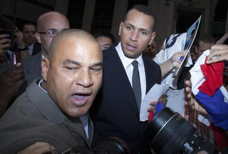 New York Yankees baseball player Alex Rodriguez looks at Fernando Mateo, the president of Hispanics Across America outside Major League Base