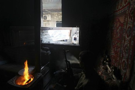 A Free Syrian Amy fighter rests in a damaged house in the Aghyol area of Aleppo January 11, 2014. REUTERS/Jalal Alhalabi