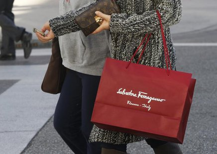 A shopper carries her purchases from the Salvatore Ferragamo boutique on Rodeo Drive, ahead of the Christmas festive season in Beverly Hills