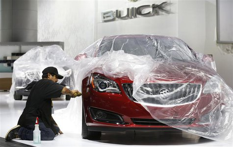 Auto show worker Jorge Martinez details a General Motors 2014 Buick Regal vehicle under wraps, as they prepare the displays for the media pr