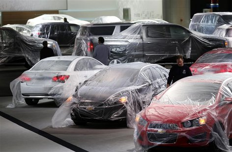 Vehicles are covered with protective wrap as workers prepare the General Motors automakers display ahead of the media preview of the North A