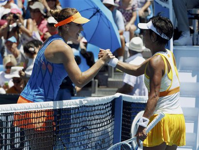 Belinda Bencic (L) of Switzerland clasps hands with Kimiko Date-Krumm of Japan at the net after defeating her in their women's singles match