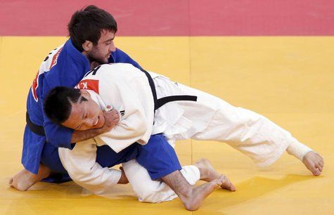 South Korea's Wang Ki-Chun fights with Russia's Mansur Isaev (blue) during their men's -73kg semi-final A judo match at the London 2012 Olym