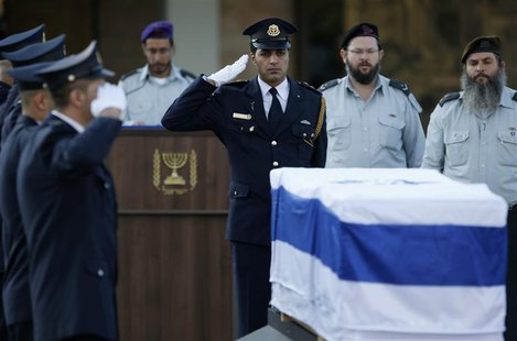 A member of the Knesset guard salutes near the flag draped coffin of former Israeli prime minister Ariel Sharon before a memorial ceremony a