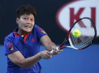 Luksika Kumkhum of Thailand hits a return to Petra Kvitova of the Czech Republic at the Australian Open 2014 tennis tournament in Melbourne
