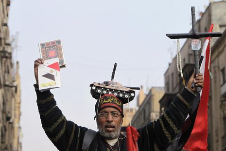 A supporter of Egypt's army chief and defense minister General Abdel Fattah al-Sisi holds a Koran (L) and a cross during a protest in suppor