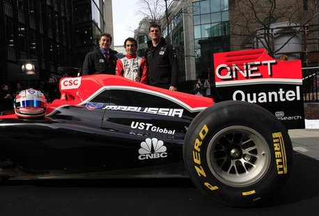CNBC presenter Ross Westgate (L), Marussia Virgin Formula One driver Timo Glock (C), and the team's Chief Executive Officer, Graeme Lowdon,