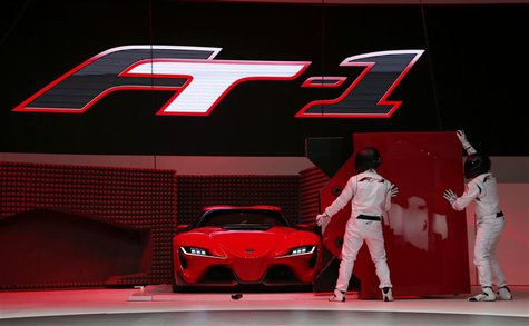 Actors perform as a Toyota FT-1 concept car is unveiled on stage during the press preview day of the North American International Auto Show