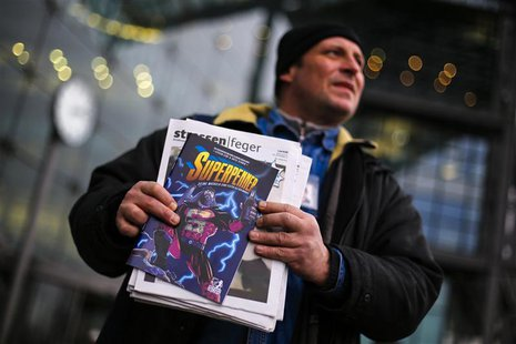 Unemployed street newspaper vendor Karsten offers the Strassenfeger (Street Sweeper) street newspaper and its Superhobo comic supplement in