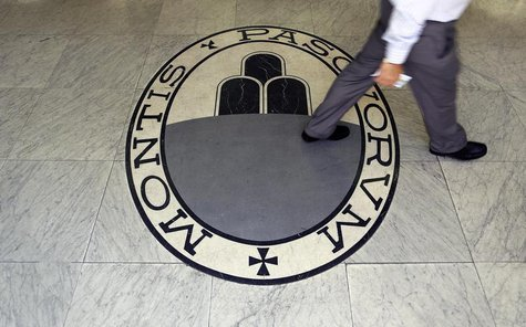 A man walks on a logo of the Monte Dei Paschi Di Siena bank in Rome September 24, 2013. REUTERS/Alessandro Bianchi