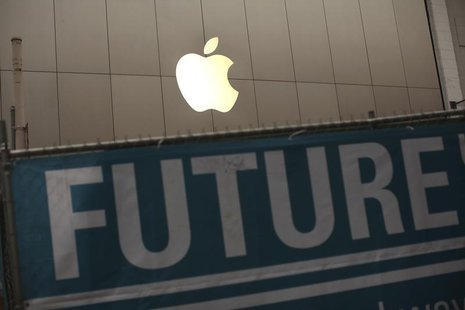 The Apple logo is pictured on the front of the company's flagship retail store near signs for the central subway project in San Francisco, C