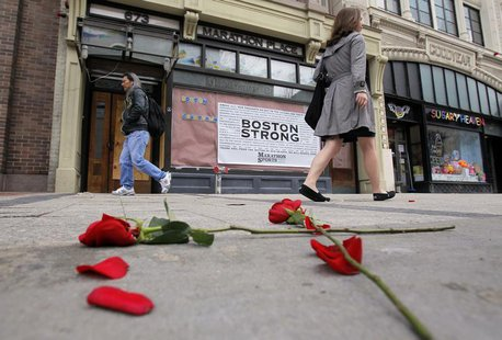 Flowers lie on the sidewalk at the site of the first explosion as people walk along Boylston Street after the street reopened to the public
