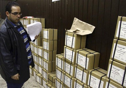 An election official stands next to boxes containing voting slips for a referendum on the new constitution in Cairo January 12, 2014. REUTER