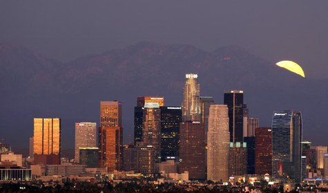 The Los Angeles downtown skyline is pictured from the Baldwin Hills State Park as a full moon rises from the San Gabriel mountains in Culver