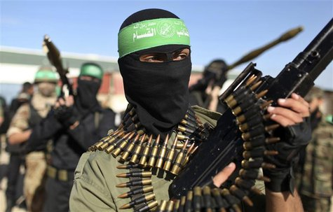 Palestinian members of the al-Qassam brigades, the armed wing of the Hamas movement, stand guard as they wait for the arrival of Hamas chief