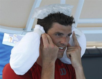 Frank Dancevic of Canada keeps cool with ice packs during a break in play in his men's singles match against Benoit Paire of France at the A