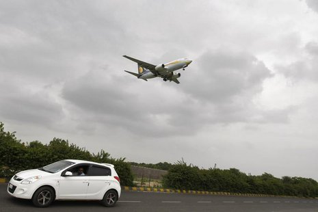 A car moves against the backdrop of a Jet Airways aircraft preparing to land at the airport in the western Indian city of Ahmedabad August 8