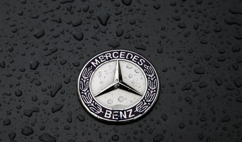 The logo of German car manufacturer Mercedes-Benz, a subsidiary of Daimler AG, is pictured covered with raindrops at a Mercedes-Benz branch