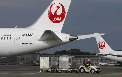 A airport worker drives a luggage transport vehicle past one of the company's Boeing Co's 787 Dreamliner plane (L) and a Beoing 767 at Narit