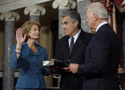 U.S. Senator Lisa Murkowski (R-AK) (L), with her husband Verne Martell (C), takes part in a ceremonial re-enactment of her swearing-in by Vi