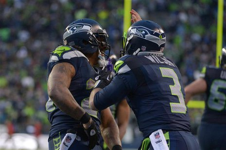Jan 11, 2014; Seattle, WA, USA; Seattle Seahawks running back Marshawn Lynch (left) celebrates with quarterback Russell Wilson (3) after sco