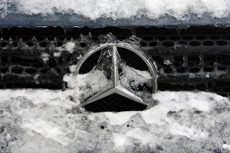 German car manufacturer Daimler's characteristic Mercedes-Benz star is seen covered with snow and ice on a vehicle in Bucharest February 10,