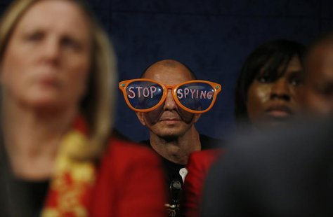 A protester against the practices of U.S. security agenices sits in the audience as U.S. Director of National Intelligence James Clapper, De