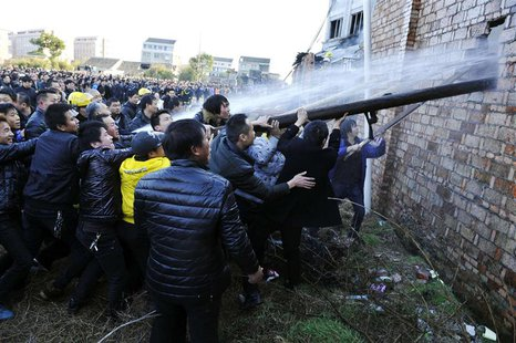 People try to break through the wall for firefighters to extinguish a fire at a factory in Wenling, Zhejiang province, January 14, 2014. REU