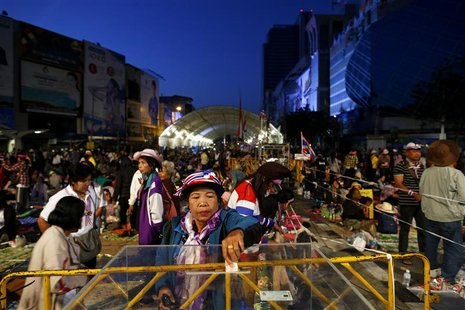 An anti-government protester gives donation as others wake up in their encampment built between shopping malls in central Bangkok January 15