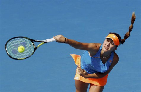Belinda Bencic of Switzerland serves to Li Na of China during their women's singles match at the Australian Open 2014 tennis tournament in M
