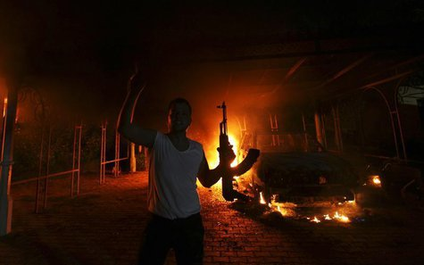 A protester reacts as the U.S. Consulate in Benghazi is seen in flames during a protest by an armed group said to have been protesting a fil