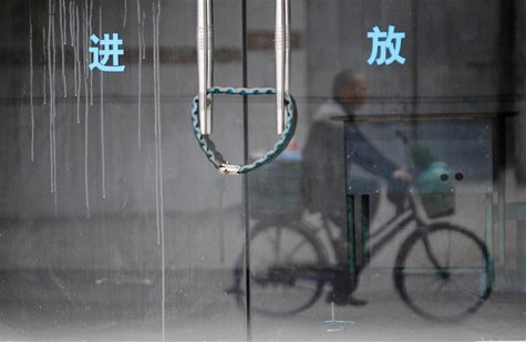 A man rides a bicycle past a closed employment bureau in Dongguan, Guangdong province 13 January, 2014. REUTERS/Alex Lee