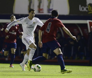 Osasuna's Miguel Flano (R) fights for the ball with Real Madrid's Cristiano Ronaldo during their Spanish King's Cup soccer match at Reyno de