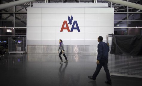 People walk past an American Airlines logo on a wall at John F. Kennedy (JFK) airport in in New York November 27, 2013. REUTERS/Carlo Allegr