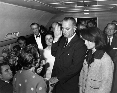Judge Sarah T. Hughes (L) administers the Presidential Oath of Office to then acting U.S. President Lyndon Baines Johnson (C) aboard Air For