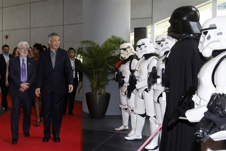 Filmmaker George Lucas welcomes Singapore's Prime Minister Lee Hsien Loong as they walk past people dressed up as Stormtroopers and Darth Va