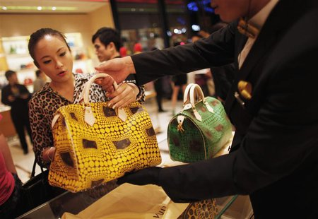 A woman shops in a Louis Vuitton store during Vogue's 4th Fashion's Night Out: Shopping Night with Celebrities in downtown Shanghai in this