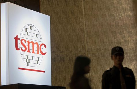 People stand behind a sign with a TSMC logo during TSMC's third quarter earnings conference in Taipei October 25, 2012. REUTERS/Yi-ting Chun