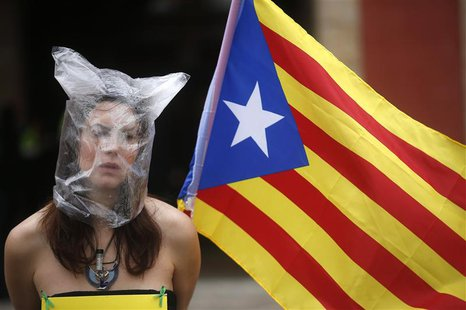 A pro-independence protestor sits in front of Catalonia's regional parliament as lawmakers voted inside, in Barcelona, January 16, 2014. REU