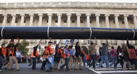 Demonstrators carry a giant mock pipeline while calling for the cancellation of the Keystone XL pipeline during a rally in front of the Whit