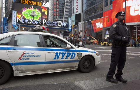A police officer stands guard in Times Square, New York December 29, 2013. The area is under increased security as the New Year's Eve celebr