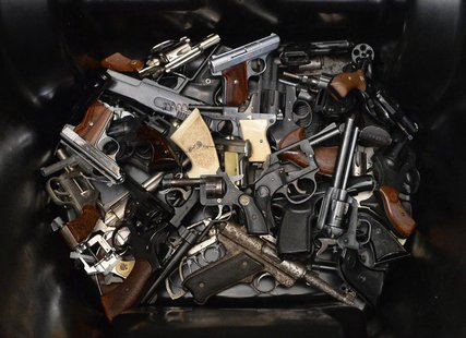 A pile of handguns are placed in a trash bin after they were surrendered during a gun buyback program organized by Mayor Eric Garcetti's Gan
