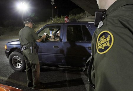 A U.S. Border Patrol agent checks the identification of a motorist at a checkpoint 20 miles north of the United States and Mexican border ne