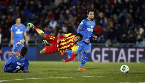 Barcelona's Neymar (C) falls as he is tackled by Getafe's Alexis Ruano (L) during their Spanish King's Cup soccer match at Colisseum Alfonso
