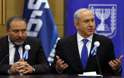 Israel's Prime Minister Benjamin Netanyahu (R) and Avigdor Lieberman attend a Likud-Beitenu faction meeting at parliament in Jerusalem Febru
