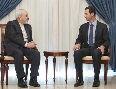 Syria's President Bashar al-Assad (R) meets Iran's Foreign Minister Mohammad Javad Zarif in Damascus January 15, 2014, in this handout relea