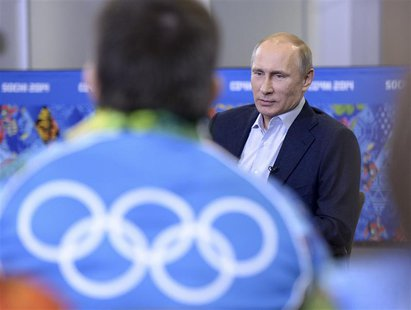 Russia's President Vladimir Putin (back) meets with volunteers who are taking part in the preparations for the Sochi 2014 Winter Olympic Gam
